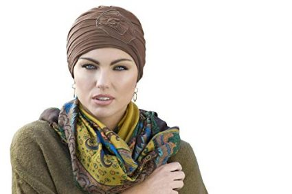 Woman wearing yellow embedded rose detail on soft chemo cap