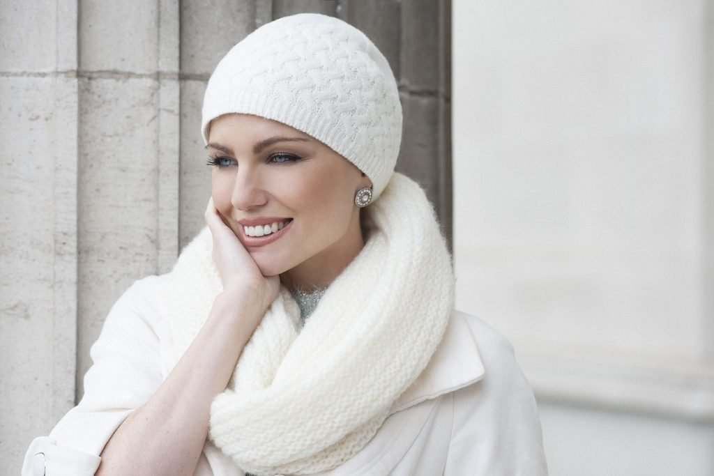 Woman wearing a soft white knitted Basketweave Stitch chemo hat