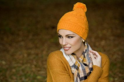 Woman wearing a soft orange Single Rib Knit beanie hat