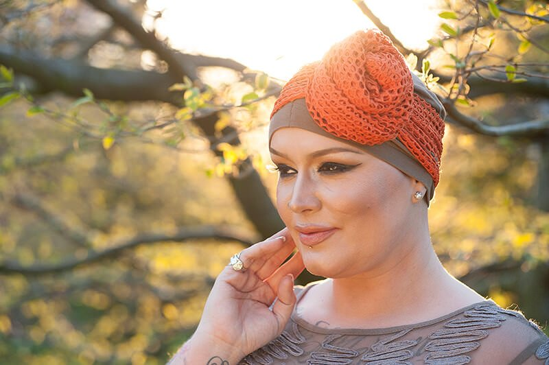 Woman wearing brown chemotherpy headwear with orange mesh scarf
