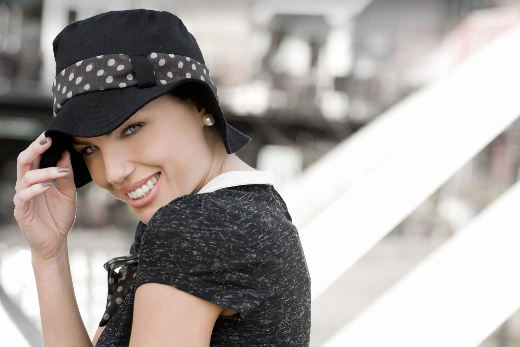 A woman wearing black sun hat with white polka dot head tie
