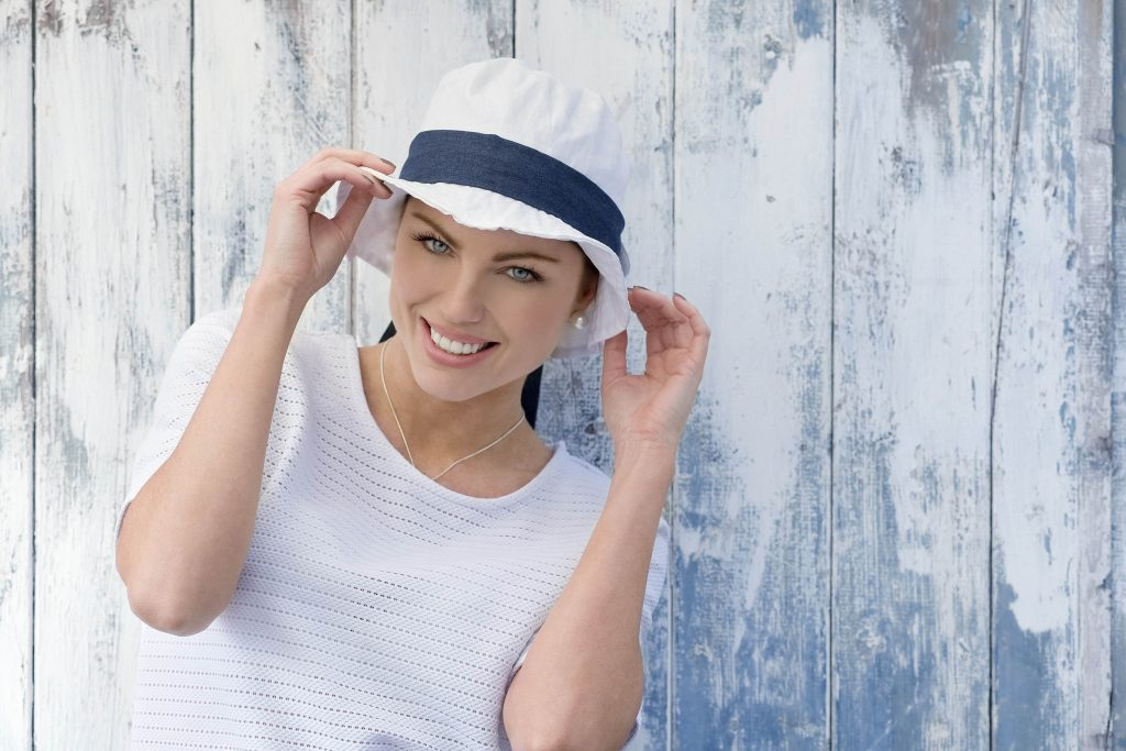 A woman wearing White sun hat with navy head tie
