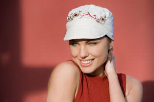 Summer hat for cancer patient Mirna Woman wearing white hat with embroidered flower pattern at the front
