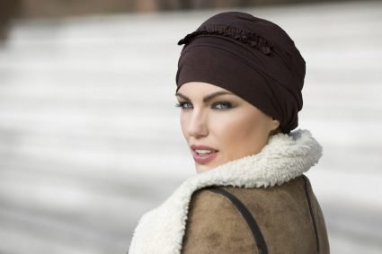 Woman wearing brown soft cheadgear for chemo patients with ruffled details at the front.