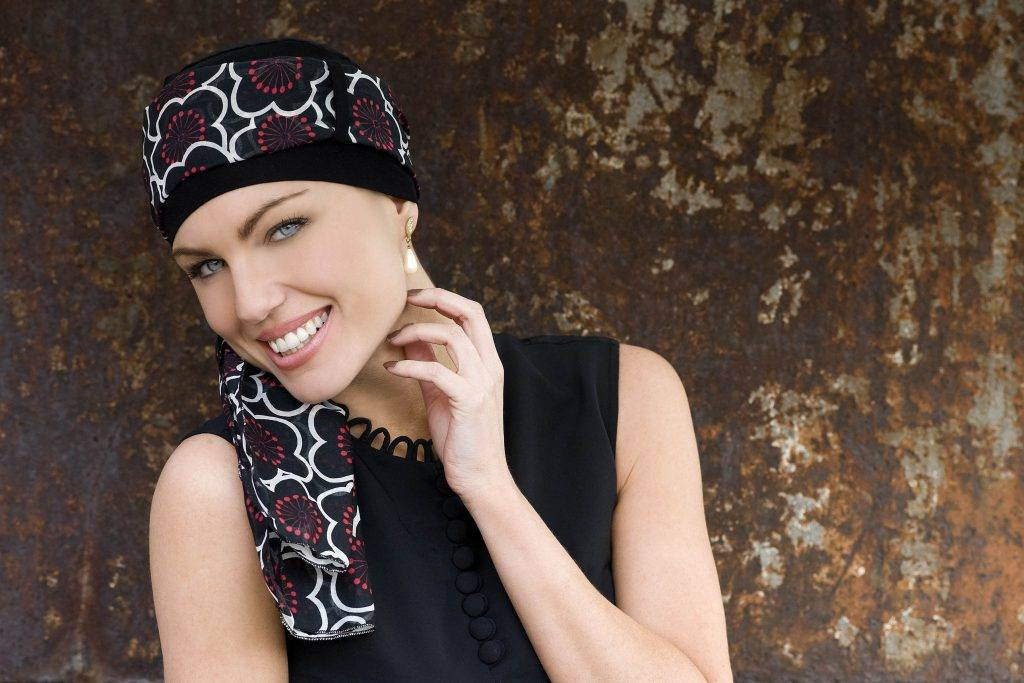 Woman wearing black cap with big flower printed head tie