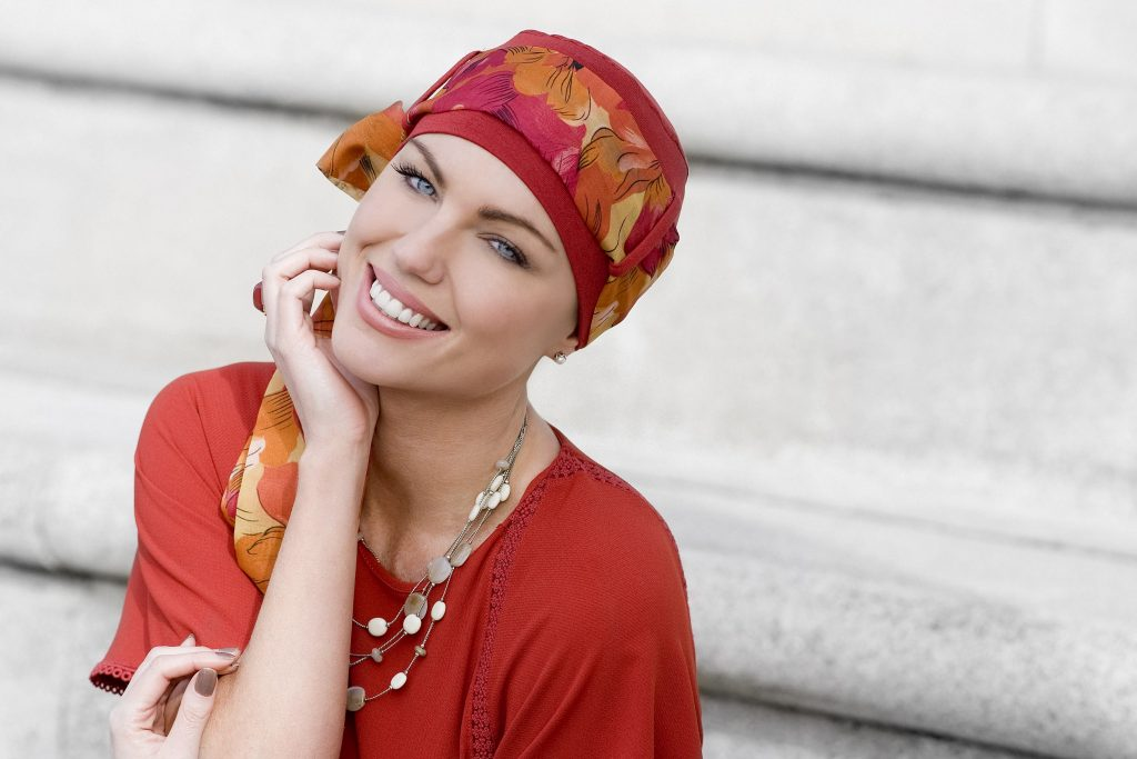 Woman wearing a red floral chemo scarf