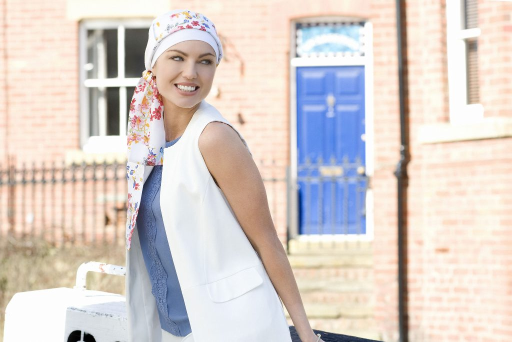 Woman wearing white chemo cap with bold flower printed head tie