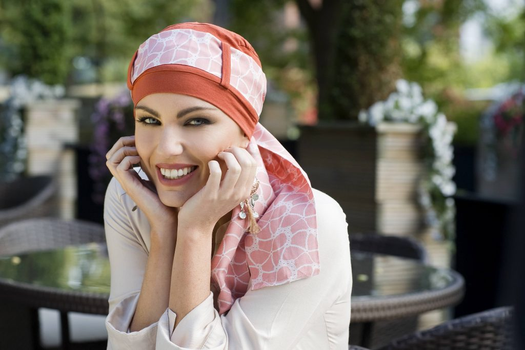 Woman wearing orange chemo scarf with floral pattern