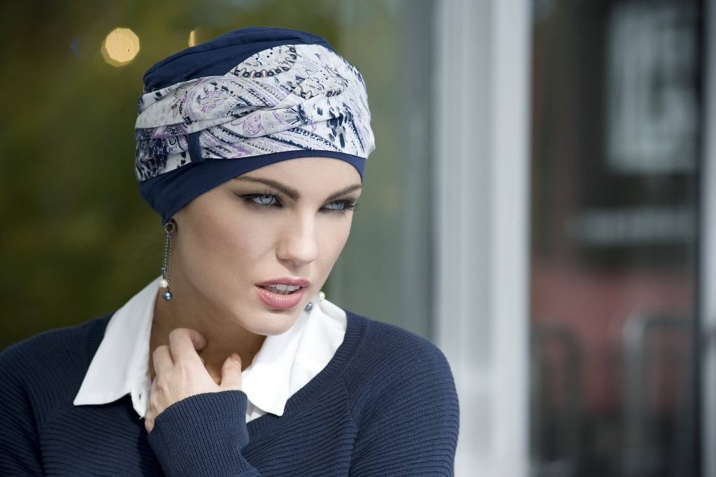 Woman wearing navy chemo headwear