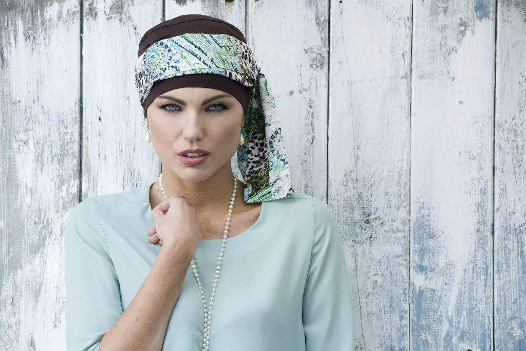 woman wearing brown chemo cap with patterned head tie