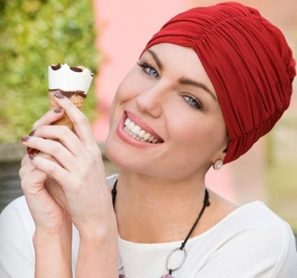 Woman wearing red soft chemo cap with ruching details at the front and the sides