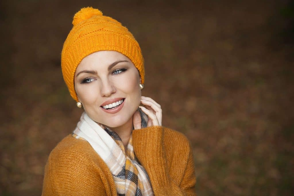 Woman wearing a soft orange Single Rib Knit beanie hat