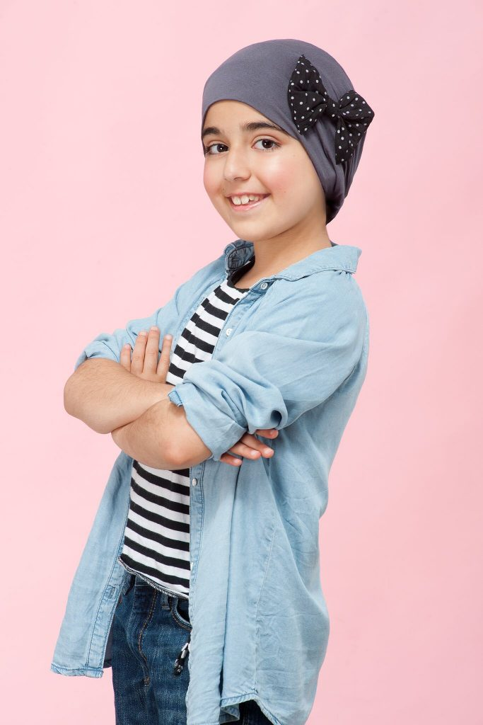 Chemo hat for children Alice grey Girl wearing a grey headwear with polka dot side bow