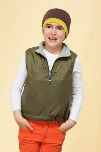 A boy wearing brown and yellow chemo cap border.