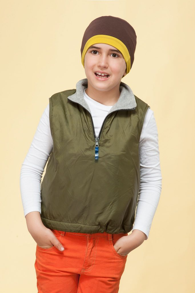 Children's cancer headwear Alex brown & yellow A boy wearing brown and yellow chemo cap border.