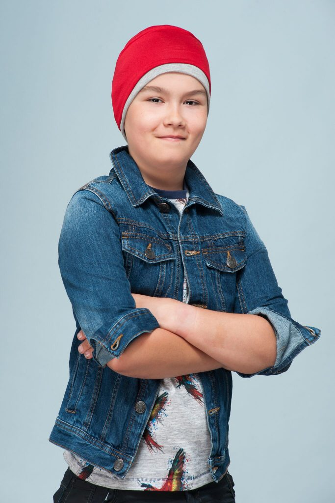 boy wearing grey and red contrast chemo hat