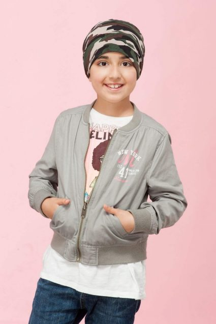 A girl wearing camo prints, layered chemo hats for kids