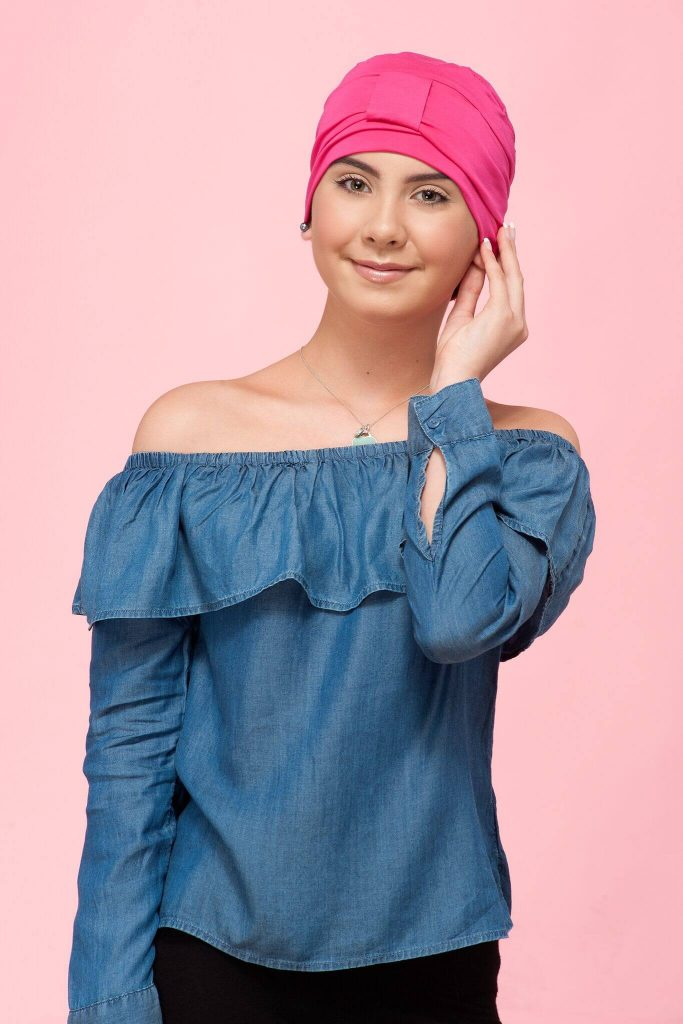 A teenage girl wearing pink soft chemo cap with tie gather at the front.
