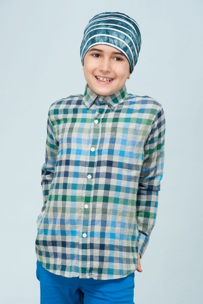 boy wearing Turquoise Blue layered chemo hat