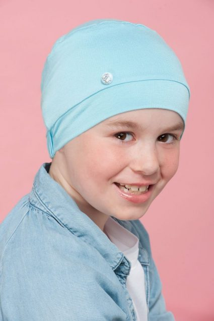 A boy wearing light blue chemo cap with customised button