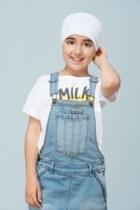A child wearing white chemo cap with white kitten button