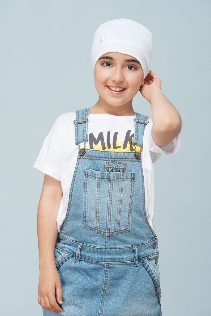Funky cancer hat for kids Milo white kitten A child wearing white chemo cap with white kitten button