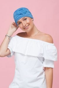 A teenage girl wearing ocean blue embedded rose detail on soft chemo cap.