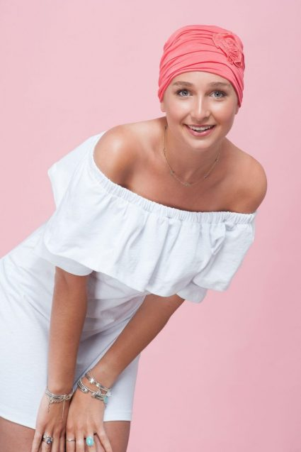 A teenage girl wearing coral pink embedded rose detail on soft chemo cap.