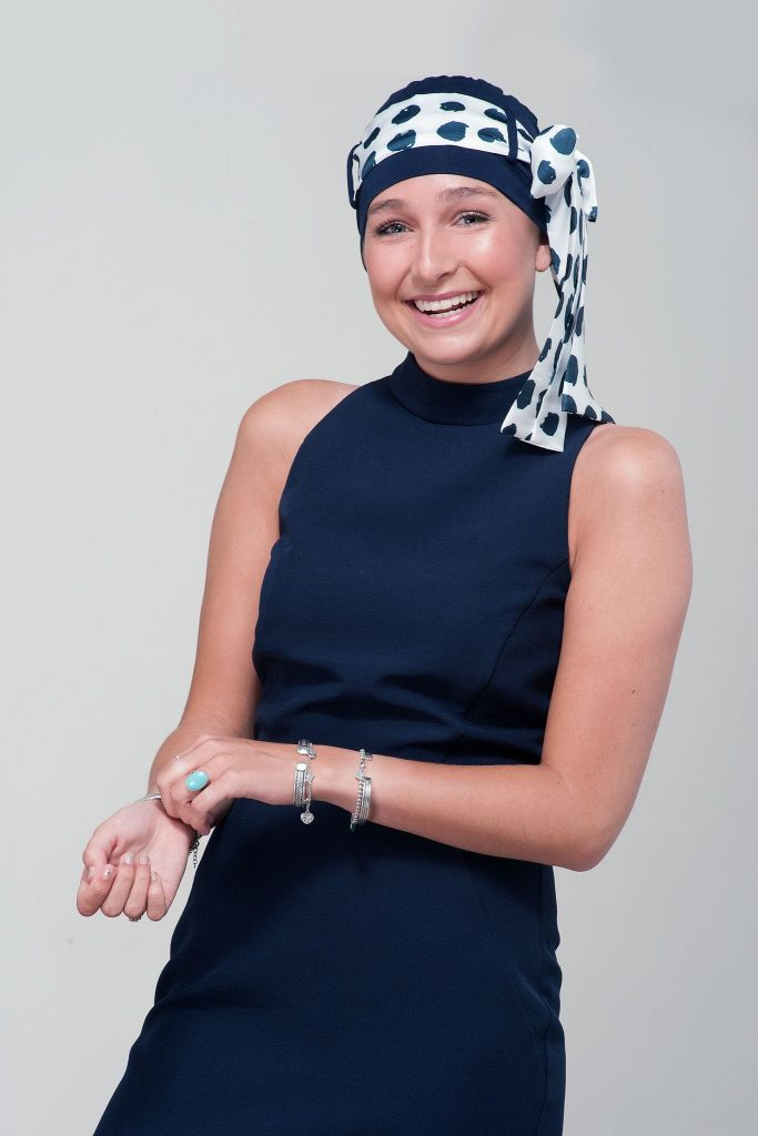 Headwear for teenage cancer patients Yanna navy white polka dot A teenage girl wearing navy chemo hat with white artistic scarf tied around in a bow form