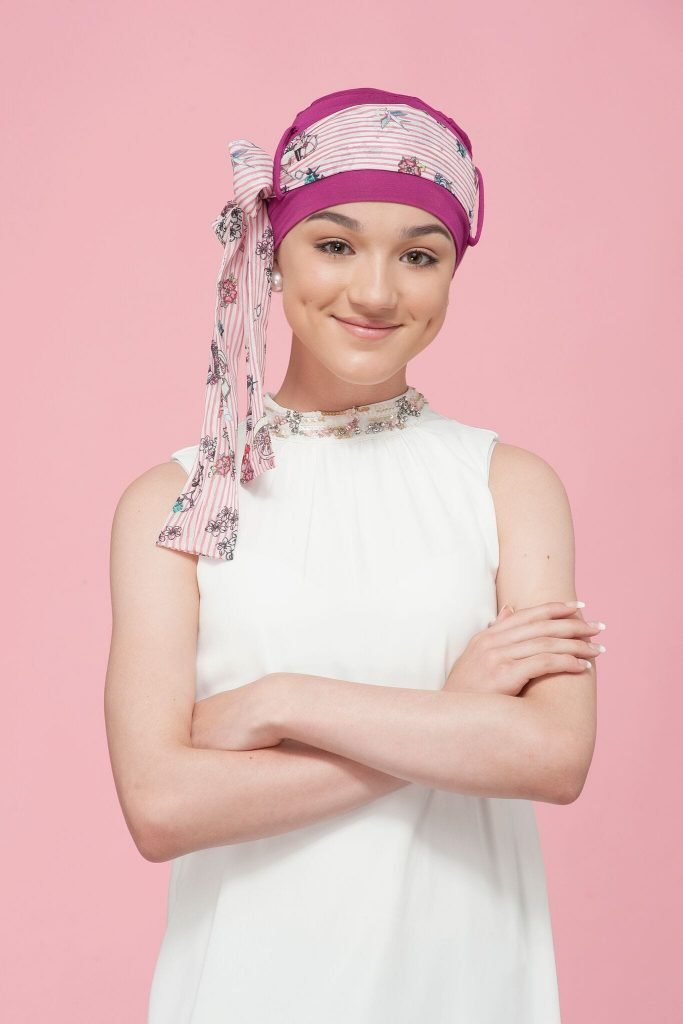 A teenage girl wearing a pink chemo cap with a floral striped scarf