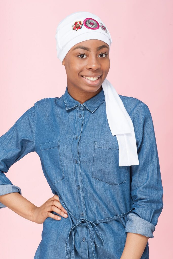 A teenage girl wearing a white chemo cap with a white and pink embellished scarf.