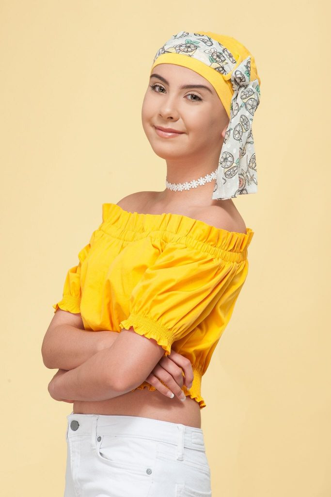 A teenage girl wearing a yellow chemo hat for girls with fruit prints on the scarf