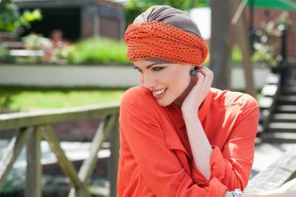Head wraps for cancer patients Daisy Taupe Orange Savana Woman wearing orange mesh scarf around a taupe chemo cap .