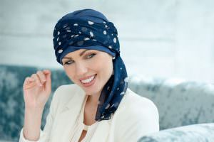 Woman wearing Navy chemo hat with polka dot scarf