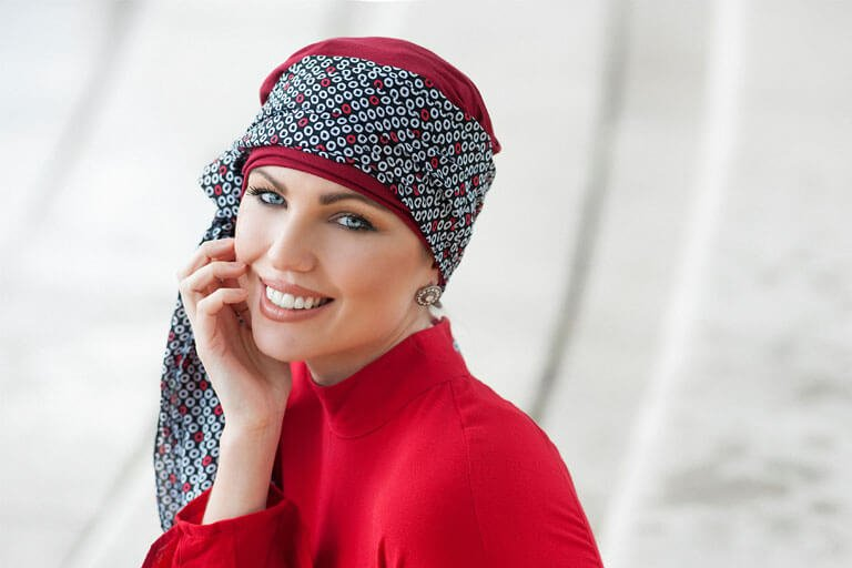 Woman wearing deep red chemo turban with attached circle printed scarf
