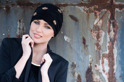 Woman wearing black and gold embellished headwear