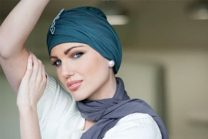 Hats for cancer patients UK Iris Woman wearing metallic grey headwear with ruffled detailing at the front