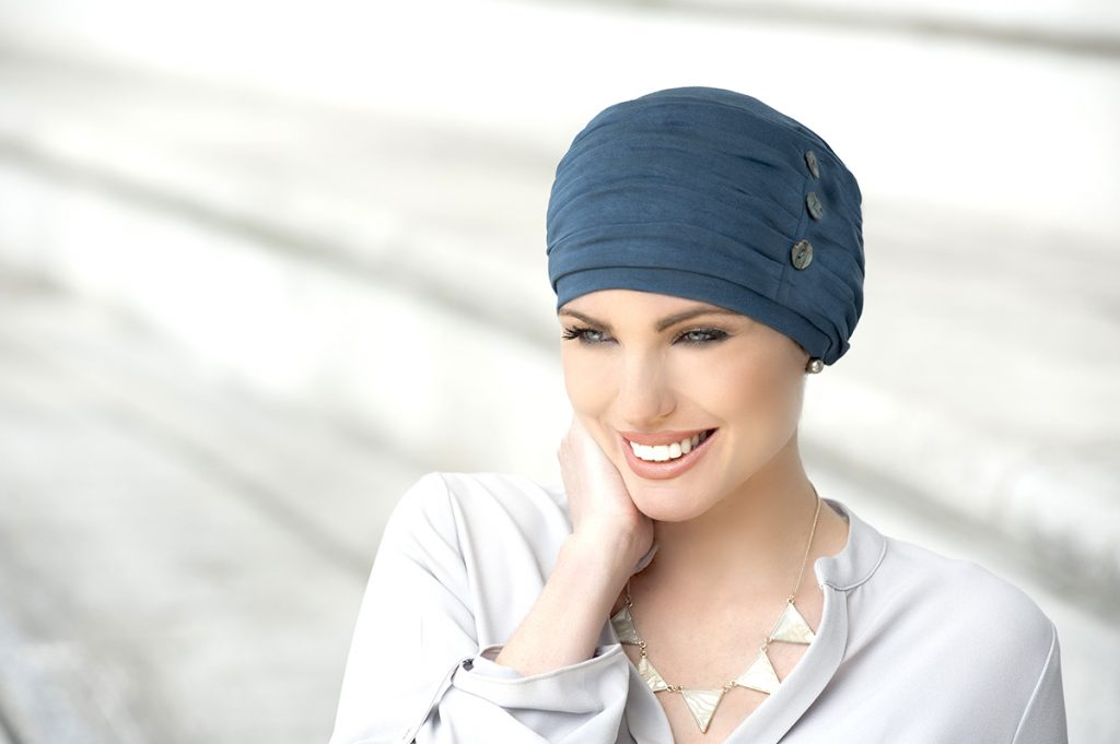 Woman wearing metallic Grey Chemo hat with buttons