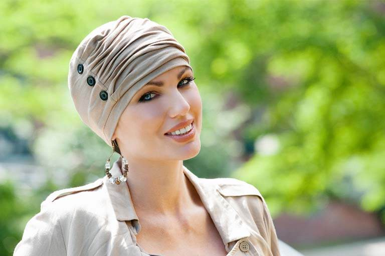 Chemo hats Louise Woman wearing light brown ruffled hat with button detailing at the side.