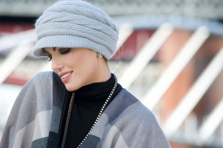 Woman wearing a soft grey knitted hat with twisted details.