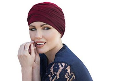 woman wearing red rose colored scarlet ruffled chemo cap