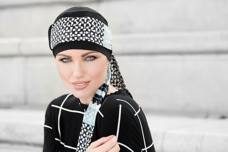 Yanna Black Midnight Pearl Woman wearing black chemo hat with blocked printed scarf