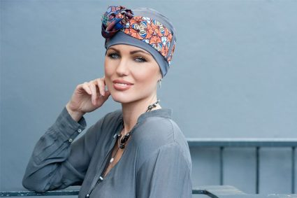 Woman wearing grey chemo hat with geometric patterned scarf