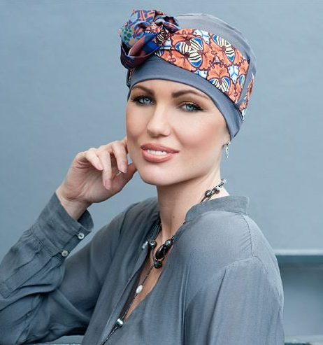 Woman wearing grey chemo hat with a geometric patterned scarf