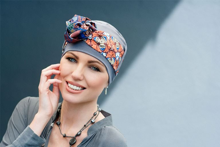 Cute Hats for Cancer Patients Yanna Grey Stone Allora Woman wearing grey chemo hat with a geometric patterned scarf.