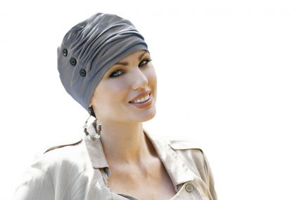 Chemo hats UK Louise Woman wearing light brown ruffled hat with button detailing at the side.