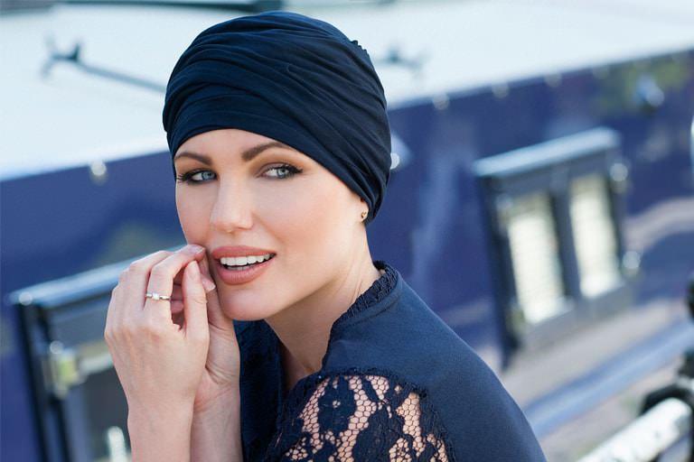 Women wearing navy chemo headwear scarlet with delicate ruffle effect.