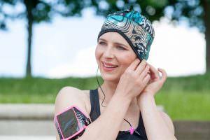 Sports chemo headwear Infinity Electric Green Sporty woman wearing a black and Electric Green wavy patterned headwear