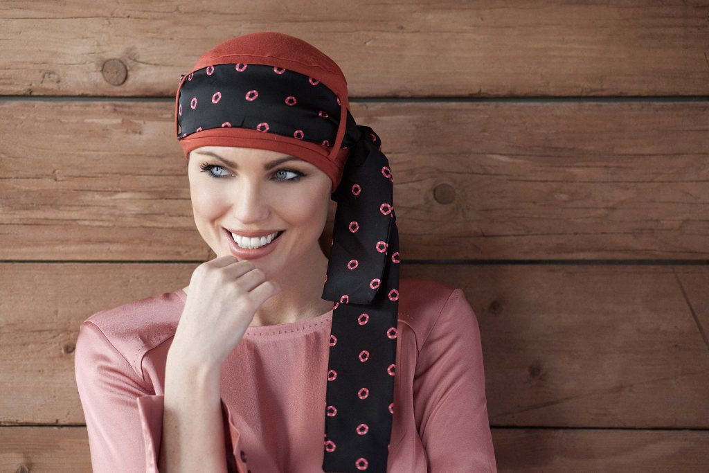 Chemo headwear for ladies Yanna Brick Diamond Rosabella Woman wearing a brick orange head cap with diamond-shaped prints on a black scarf