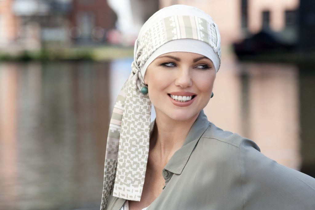 Woman wearing Bamboo chemo hat ivory green headwear with printed bow tie